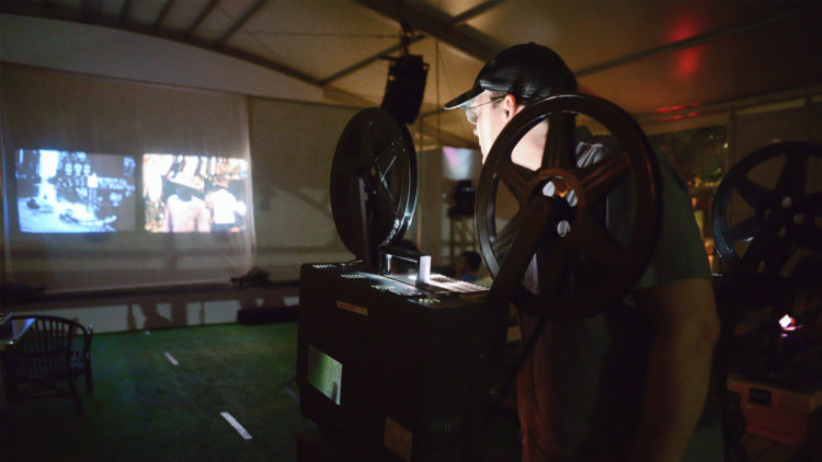 Archive films being projected onto a screen during the 2015 Miami Book Fair