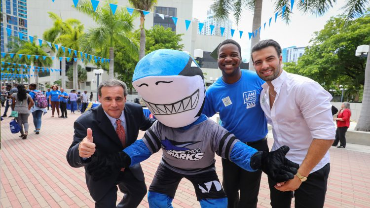 Miami City Commissioner Frank Carollo with Shark mascot, a student and MDC alumnus, singer Jencarlos Canela.