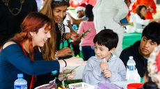 volunteer helping children build crafts