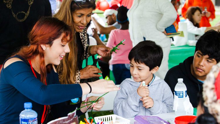 volunteer helping children build crafts