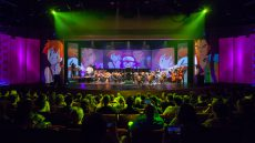 Ochestra onstage with video projections and audience