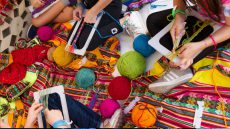 Kids work with bright balls of yarn