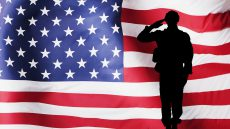 graphic: american flag background with silhouette of soldier saluting in front