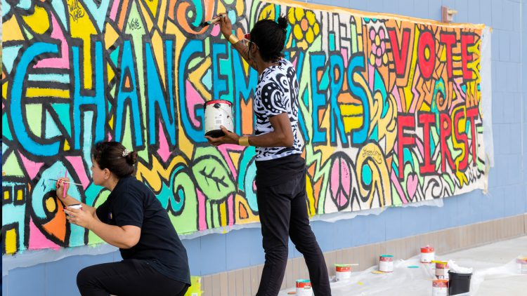 Students work on a wall mural