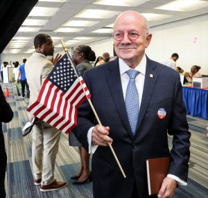 MDC President, Eduardo Padron holds American flag and votes at North Campus