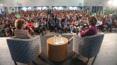 Author and Interviewer sit on stage with audience looking on