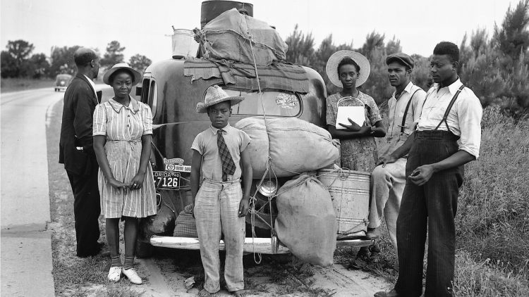 Group of Black migrants standing around their car