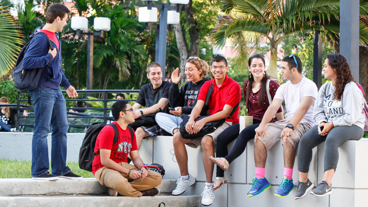 Group of students sitting by stairs outdoor