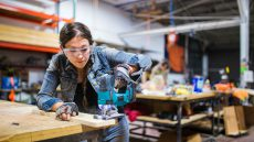 Young woman using a power tool