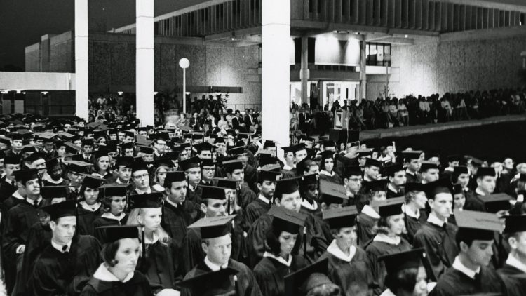 Graduates assembled under two porticos of the Niles Trammell Learning Resources Center building