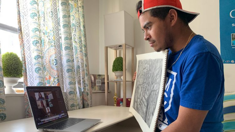 Male student showing drawing on video call