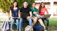 Latinx students sitting under a tree