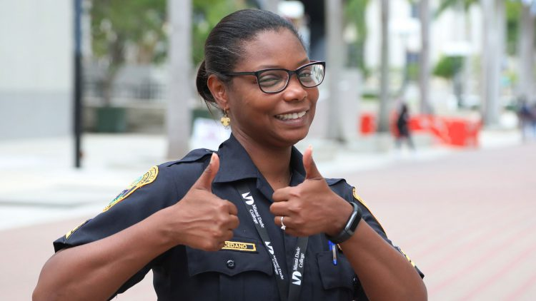 MDC security staff Lucia Cedano smiles and gives two thumbs up