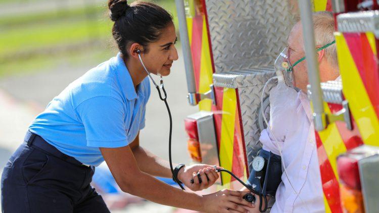 EMT student assisting elder man