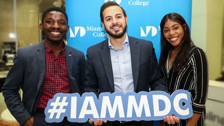 Giovanni R. Castro and two other alumni holding a sign that reads #IAMMDC