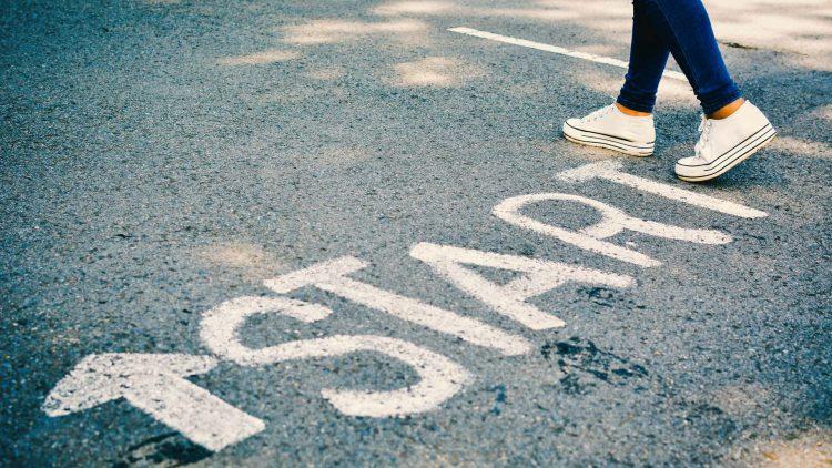 "Woman's feet on pavement with ""Start"" written on it."
