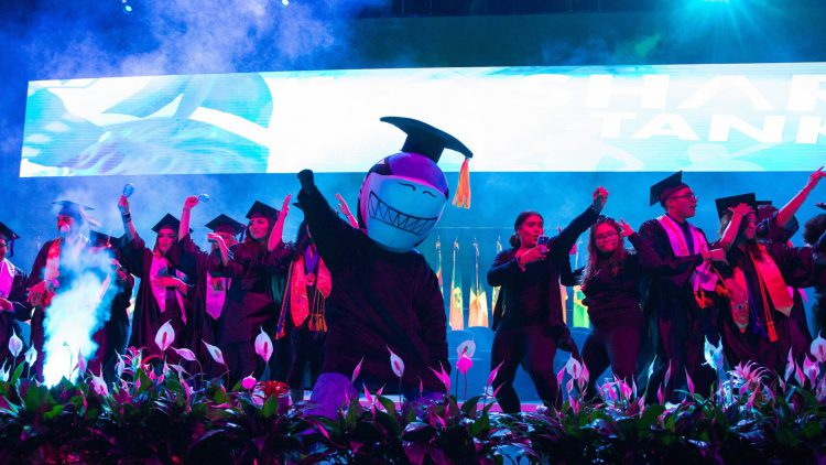 Graduating students onstage with college shark mascot