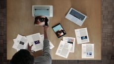 overhead shot of man with laptop and publication pages
