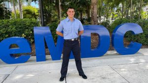 Portrait of Mikael Alfonso standing in front of MDC sign