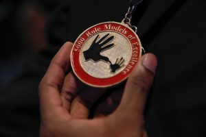Close up of hand holding medal with inscription 5000 Role Models of Excellence
