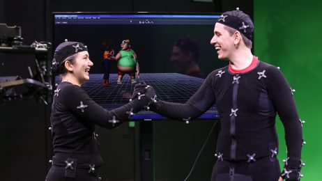 Male and female student in front of green screen with motion capture technology