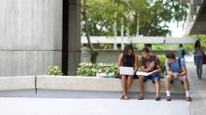 Three students sitting outside on campus