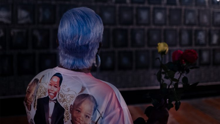 Photo from behind of woman with blue hair looking at artwork