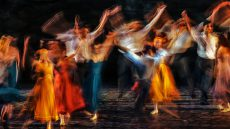 Motion blurred dancers on stage in colorful costumes
